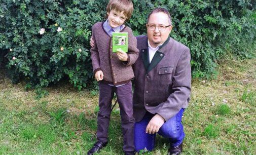Vater und Sohn präsentieren gemeinsam erstelltes Wanderbuch